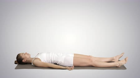 mantra : Yoga meditation laying on a mat with closed eyes on gradient background.