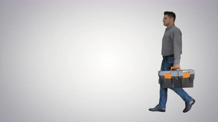 ремонтник : Professional repairman concept Handyman walking with tool case on gradient background.