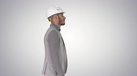 supervisor : Architect in white helmet walking on gradient background.