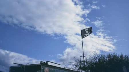 roger : Black pirate flag flutter on wind with partly overcast blue sky. Jolly Roger sign on building inland.