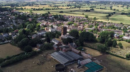 cow flies : Aerial view, zoom on tower. Old settlement in England with stone church and farm.