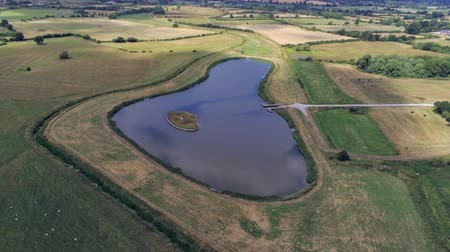 chester : Aerial view, zoom in. Drone panorama of plains and small pond hidden between fields Stock Footage