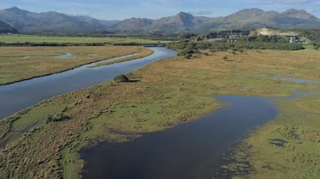 taş ocağı : Aerial view, zoom in and forward move. Drone panorama over Glaslyn reserve wetlands,quarry, bridge and mountains in background in sunny Wales Stok Video