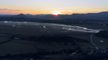 calming : Aerial view, zoom in and pan move. Drone panorama sunset over hills, sea, Snowdonia mountains in background in North Wales