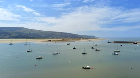 cerceta : Aerial view, rise up move. Drone panorama over low tide sea, shore, bay, boats in Barmouth, Wales
