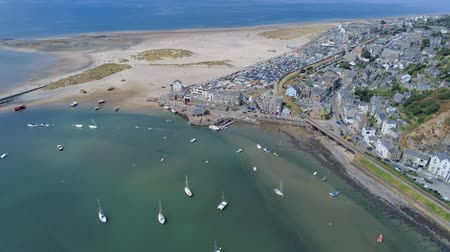 ancorado : Aerial view, sideways move. Drone panorama over sea, harbor, beach and downtown of Barmouth, Wales Stock Footage
