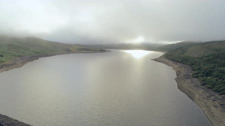 yüksek ova : Aerial view, fast pan move. Drone panorama of Llyn Celyn water reservoir with dam and sheep on grass in Wales Stok Video