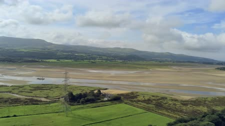 yüksek ova : Aerial view, pan move. Drone panorama of sea bay during low tide in Wales Stok Video