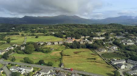 yüksek ova : Aerial view, rise up move. Drone panorama of Penrhyndeudraeth town in Snowdonia mountains in Wales Stok Video