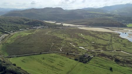 yüksek ova : Aerial view, pan move and zoom. Drone panorama of sea bay during low tide in hilly Wales