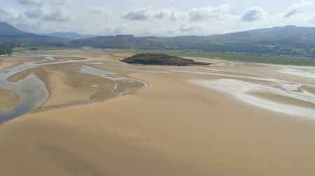 yüksek ova : Aerial view, forward move. Drone panorama of Grifftan island on low tide sea in Snowdonia mountains in North Wales