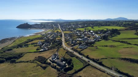 oldalt : Aerial view, pan move. Drone panorama of sea with silhouette of Criccieth castle, grass fields, road and town in background