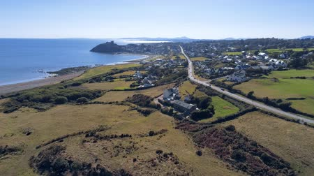 sideways : Aerial view, static and sideways move. Drone panorama of sea with silhouette of Criccieth castle, cars on road and town in background