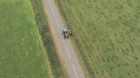 perspectives : Aerial view, down move and pan. Converted tractor with trimmer trims hedges on straight road between fields