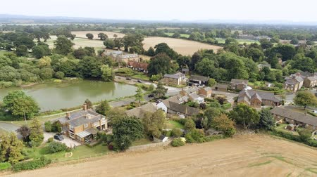 yüksek ova : Aerial view, sideways move. Christleton houses next to pond. Village in Cheshire countryside.