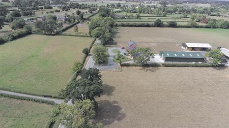 английский парк : Aerial view, static and rise up move. House and farm with warehouse building among fields in Cheshire. Dry grass during hot summer Стоковые видеозаписи