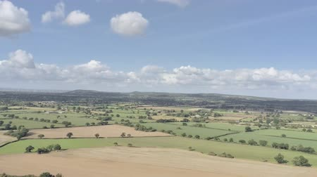 yüksek ova : Aerial view, tilt up and zoom move. Cheshire fields with Merseyside in background on a sunny day Stok Video