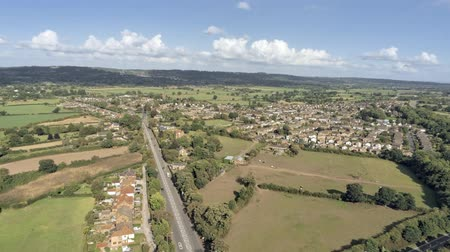 settlement : Aerial view, tilt down move. Traffic on roundabout, houses and fields in Tarvin on Cheshire countryside Stock Footage