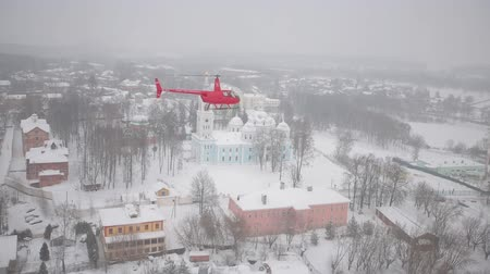 mi : A red helicopter is flying over the snowy city. Stock Footage