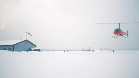 heliport : A red helicopter sits on a snow-covered field.