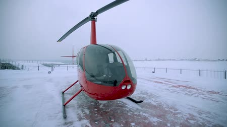 heliport : A red helicopter stands on the landing site in winter.