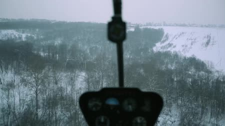 mi : A red helicopter is flying over a snowy forest.