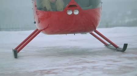 heliport : A red helicopter takes off in a snow-covered field.