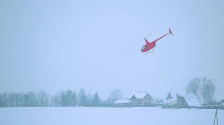 heliport : Red helicopter takes off in winter over the power line. Stock Footage