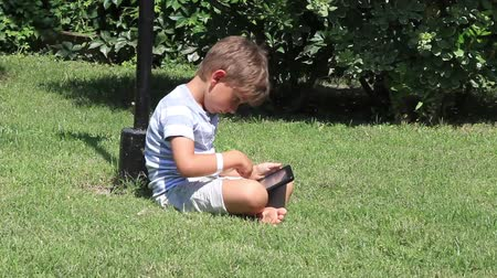 pedleri : The boy reads the e-book Stok Video
