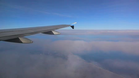 düzlem : View looking out the window of an airplane flying over the east coast with clouds moving serenely under the plane.