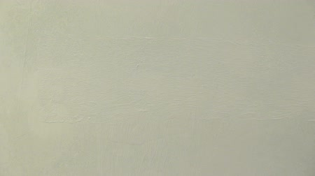 Painting the wall with white paint, horizontal strokes
