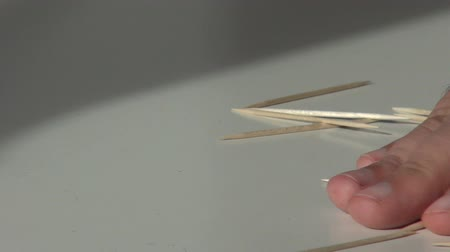 man hand removes toothpicks scattered on the table