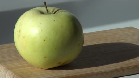 green apple is put on a wooden cutting board and taken Dostupné videozáznamy