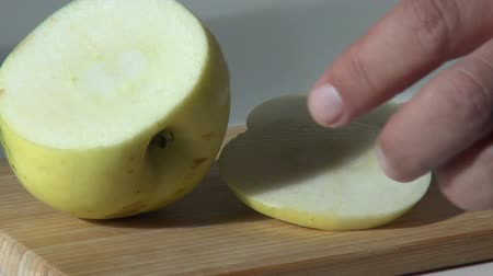 cortadas : pieces of cut green apple on wooden cutting board