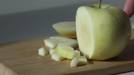 pieces of cut green apple on wooden cutting board