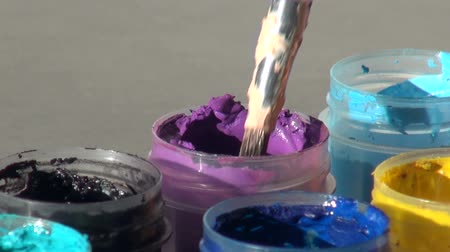 гуашь : brush immersed in a jar of purple violet Acrylic gouache paint.