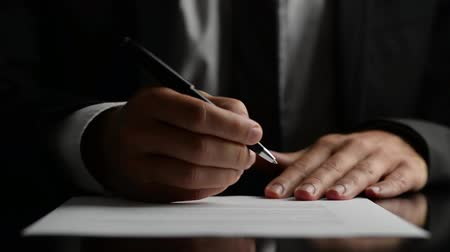 advokát : Businessman signing a document or contract with a close up view of his hand with the pen and sheet of notepaper on a desk top. Over black background.
