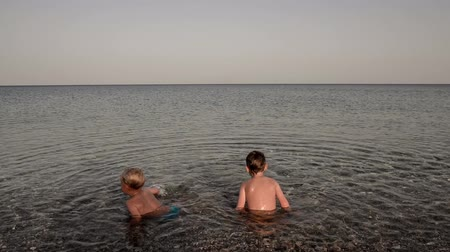 rhodes : Two toddler boys enjoying summer holidays in the shallow sea with pebbles. Stock Footage