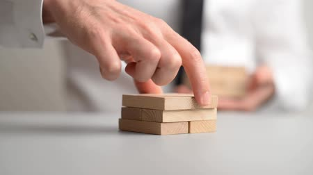 стремление : Businessman stacking wooden pegs in a conceptual video of business vision and idea.