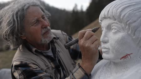 ручная работа : Senior sculptor carving portrait of a man in a white stone.