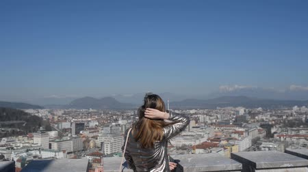 slovenya : Video of a young woman on Ljubljana castle tower looking down at a beautiful city of Ljubljana. Stok Video