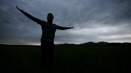 realization : Young man enjoying life under cloudy evening sky turning around with arms spread widely.