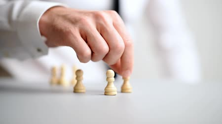 metaphors : Video of businessman placing pawn chess figures on white table. Stock Footage