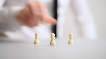 trabalho em equipe : Hand of a businessman positioning chess pawn pieces in to a pyramid structure in a conceptual footage of business recruitment and teamwork.