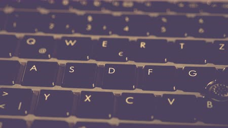 compelling : Black Computer keyboard extreme close up UHD stock footage. A black computer or laptop keyboard in macro close up with a sliding camera move and subtle dim lighting for artistic effect.