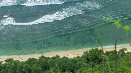 puré : Top view perspective of waves rolling one by one to the Nunggalan Beach, Uluwatu, Bali, Indonesia Stock Footage