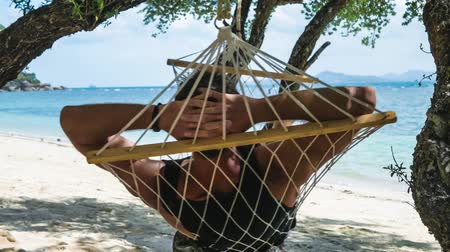 релаксация : Man swinging relaxed in a hammock on the beach in front of the beautiful blue ocean and other island in background. Hiding from the sun in the shadow of a tree.