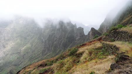 nezkažený : Fog flowing over their edges of mountain peaks. Amazing mountain scenery in Xo-Xo Valley. Santo Antao Island, Cape Verde Cabo Verde 4k video