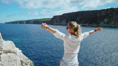 растягивается : Woman in white in front of blue sea raising arms enjoying freedom during summer holidays vacation travel in Greece. Happy free Caucasian female . HD video slow motion Стоковые видеозаписи