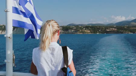 Cruise ship vacation in Greece. Young woman leaving greek island on cruise boat at sea. Romantic travel at sea looking at beautiful seashore. Slow motion HD